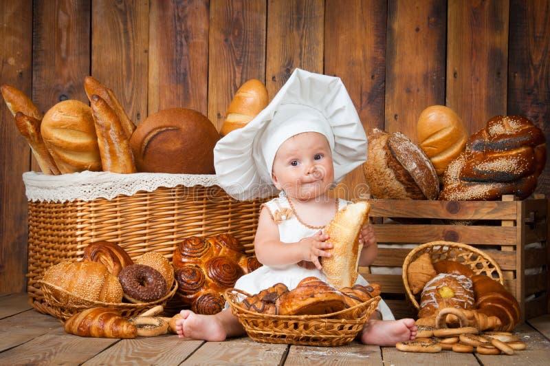 A criança pequena cozinha um croissant no fundo das cestas com rolos e pão fotografia de stock royalty free