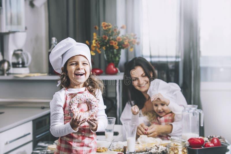 A criança pequena da menina come uma filhós com meu cozinheiro feliz da mamã e da irmã foto de stock