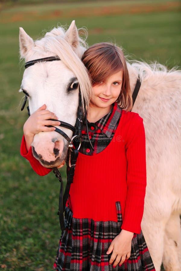 Criança pequena da moça que abraça um pônei branco em no sua cabeça e sorriso foto de stock royalty free