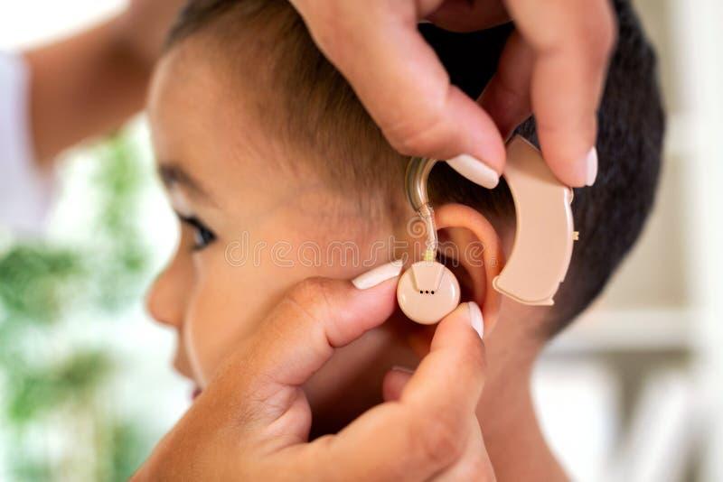 Criança pequena de ajuda para ouvir outra vez o som fotos de stock royalty free