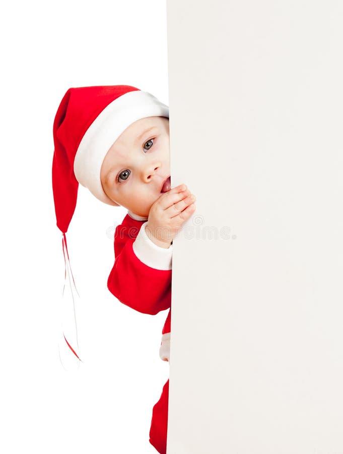 Criança pequena de Santa que olha do cartaz de trás foto de stock