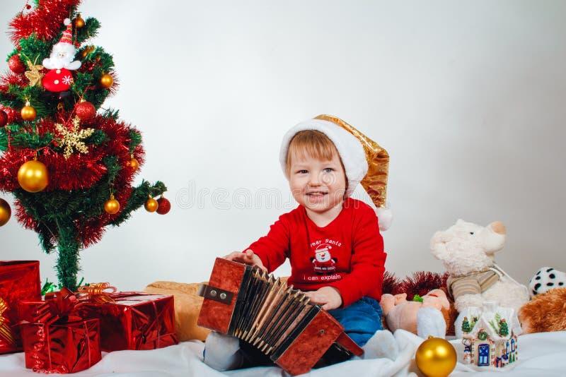 Criança pequena de sorriso em um traje do Natal com um acordeão em suas mãos que sentam-se sob a árvore de Natal imagens de stock royalty free
