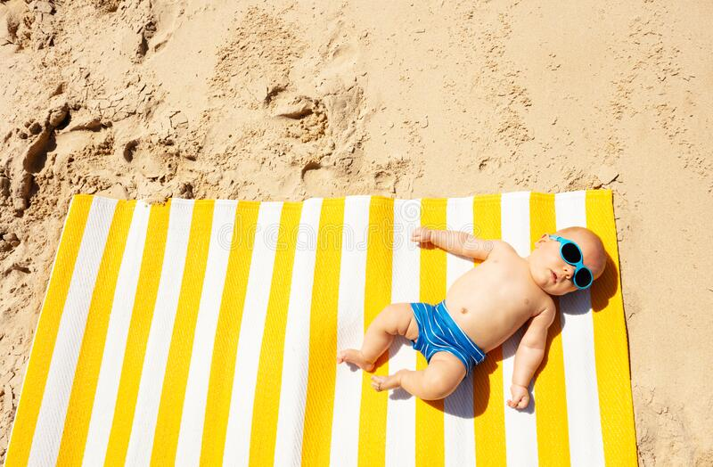 Criança pequena deita no tapete de praia de cima fotos de stock royalty free