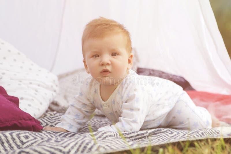 Criança pequena do bebê do infante recém-nascido em uma manta no parque verão SU imagens de stock