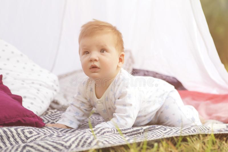 Criança pequena do bebê do infante recém-nascido em uma manta no parque verão SU imagem de stock royalty free