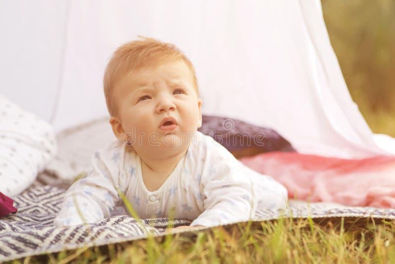 Criança pequena do bebê do infante recém-nascido em uma manta no parque verão SU fotos de stock