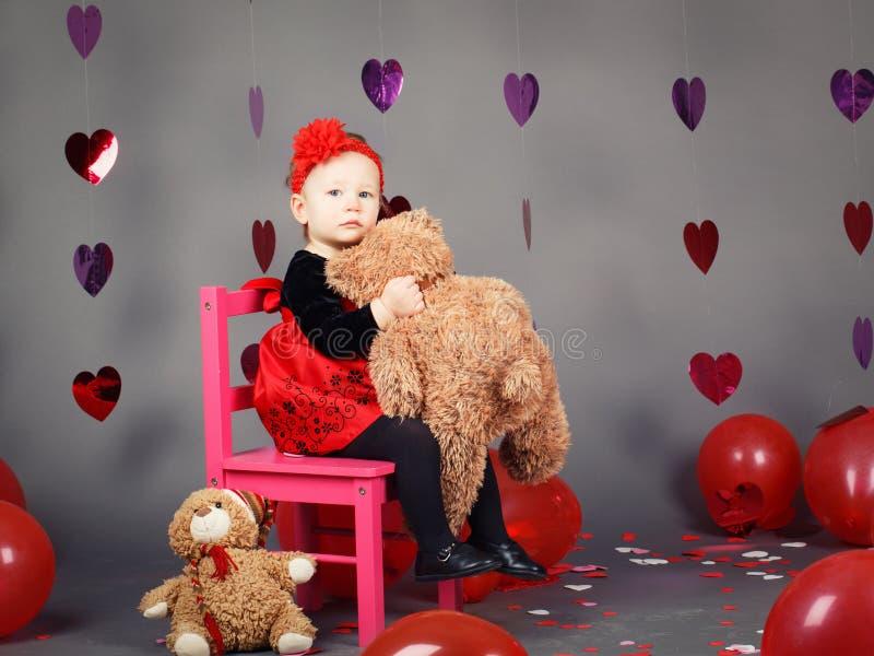 Criança pequena do bebê que senta-se na cadeira cor-de-rosa pequena com o brinquedo do urso no estúdio fotografia de stock royalty free