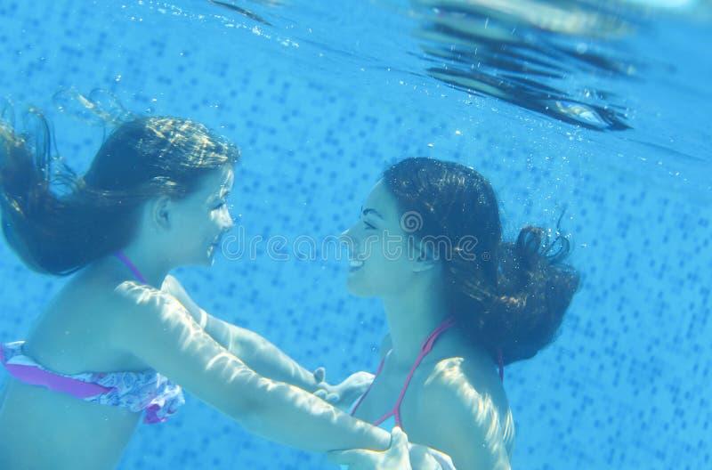 Criança pequena e jovem mulher subaquáticas na piscina fotos de stock royalty free