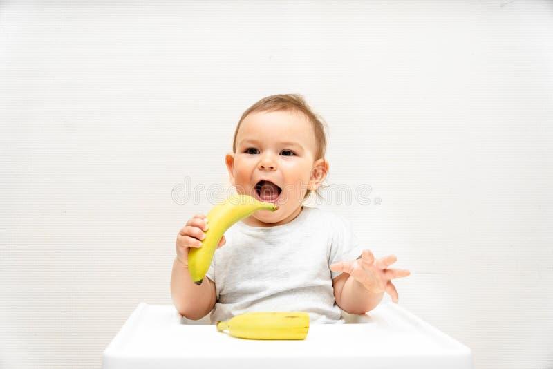 Criança pequena engraçada que come a banana em um bebê do alimento de espaço da cópia da cadeira alta imagens de stock