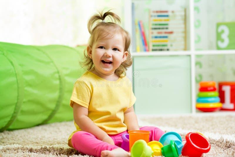 Criança pequena engraçada que joga com brinquedos foto de stock