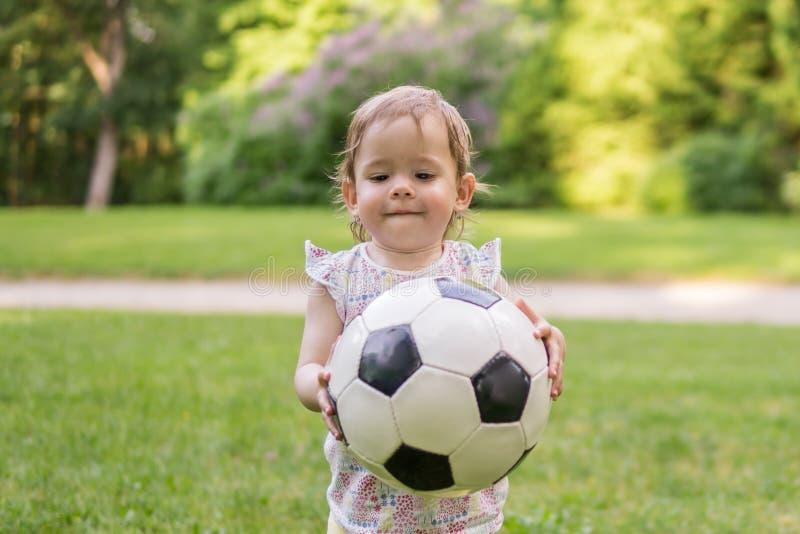 A criança pequena está jogando com a bola do futebol no parque fotos de stock royalty free