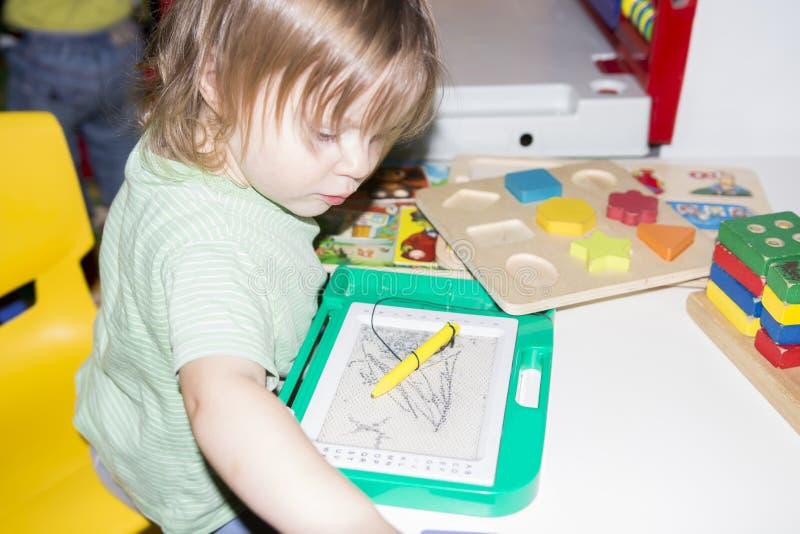 A criança pequena está jogando com os brinquedos na sala do ` s das crianças Criança no jardim de infância imagens de stock