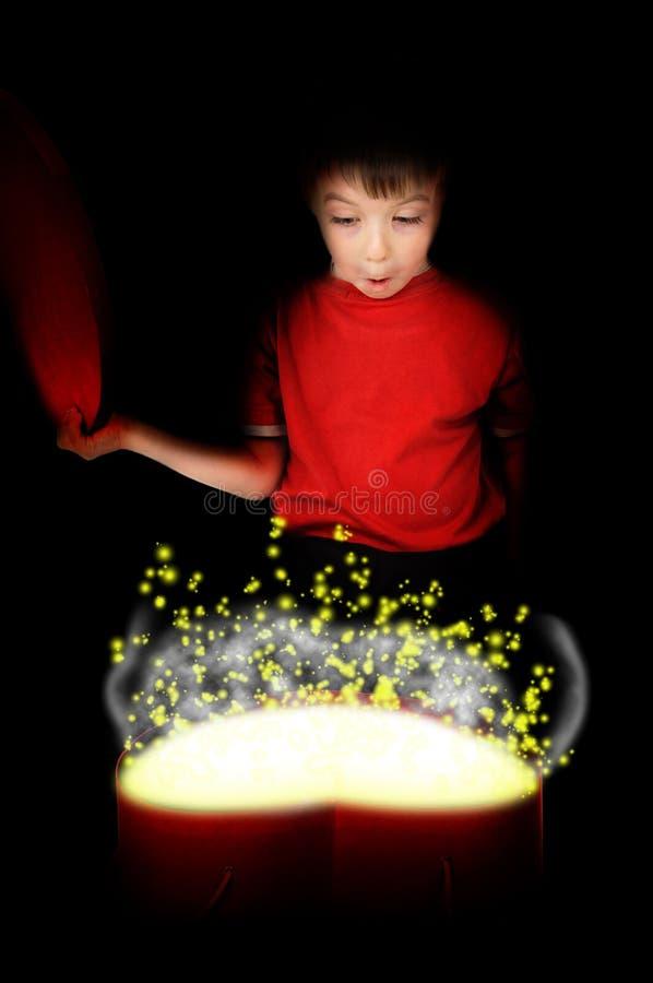 A criança pequena feliz abriu a caixa sob a forma do coração imagem de stock