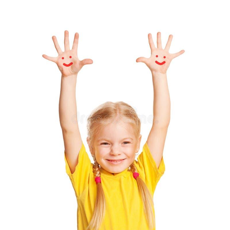 Criança pequena feliz com as faces do smiley pintadas em suas palmas. foto de stock royalty free