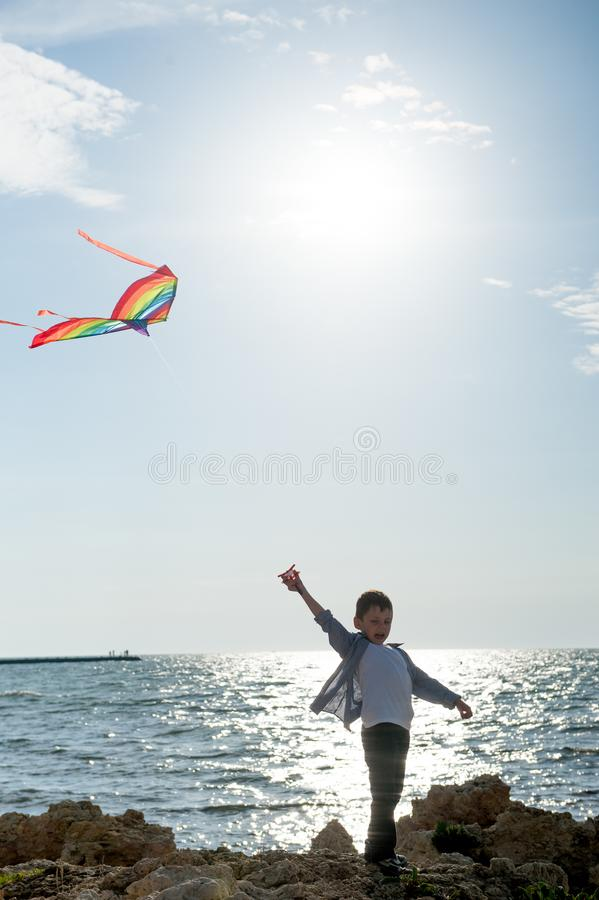 Criança pequena feliz com o papagaio do voo perto do por do sol do mar no dia de verão imagem de stock