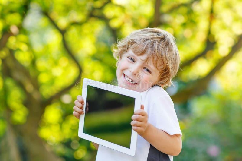 Criança pequena feliz de sorriso que guarda o PC da tabuleta, fora imagem de stock