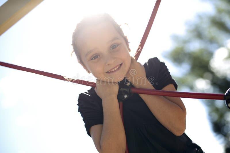 Criança pequena feliz escalada no campo de jogos fotografia de stock royalty free
