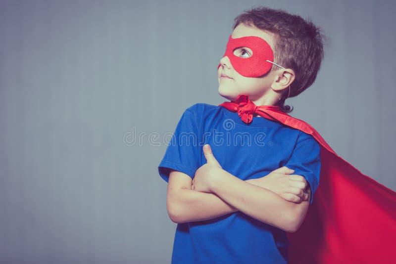 Criança pequena feliz que joga o super-herói imagens de stock royalty free
