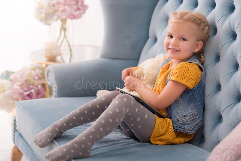 Criança pequena feliz que senta-se no sofá imagem de stock royalty free