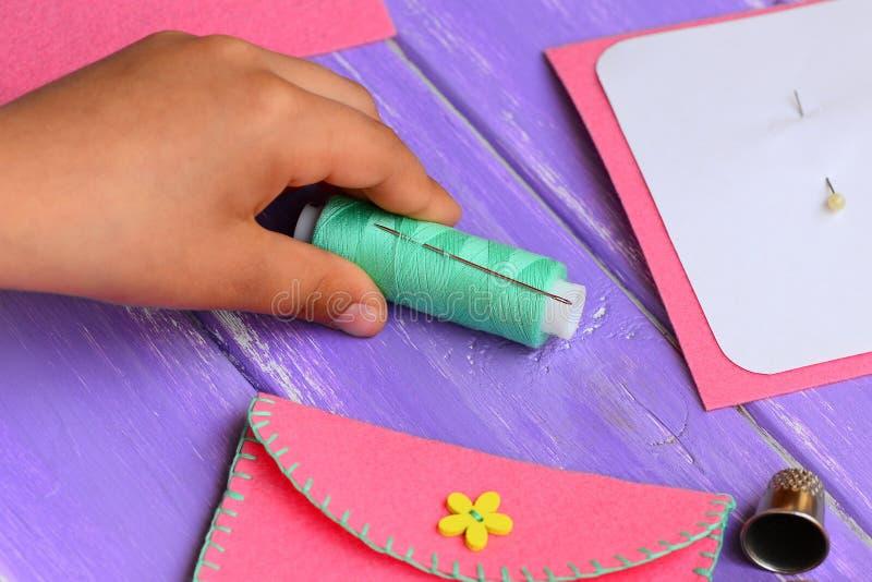A criança pequena fez uma bolsa de feltro Costurando fontes em uma tabela de madeira Ofício engraçado e simples da costura para q imagem de stock royalty free
