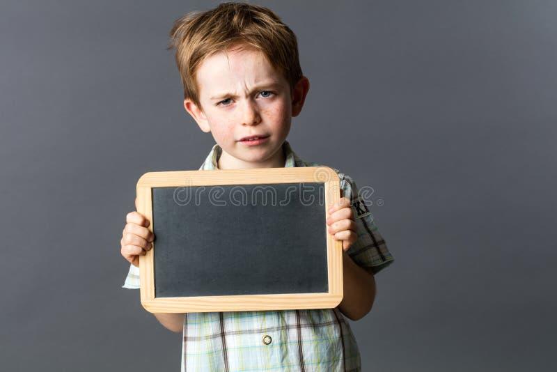 Criança pequena infeliz que mostra a ardósia vazia da escrita à reflexão expressa foto de stock