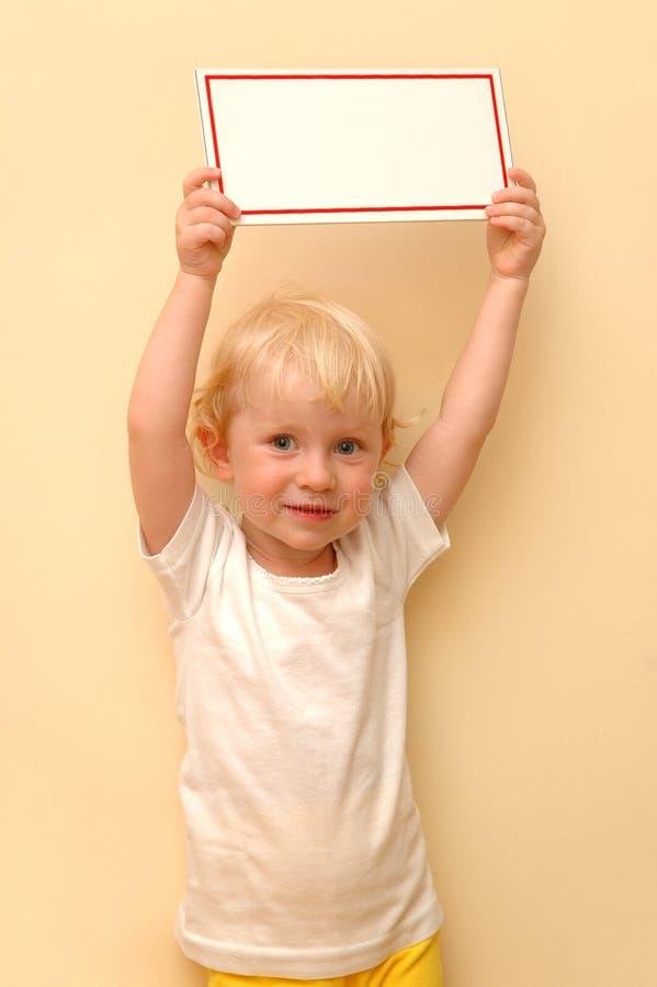 A criança pequena mantem a tabuleta nas mãos foto de stock royalty free
