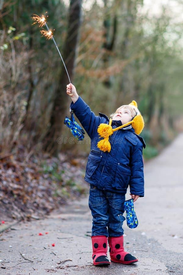 A criança pequena no inverno veste guardar chuveirinho ardente fotos de stock