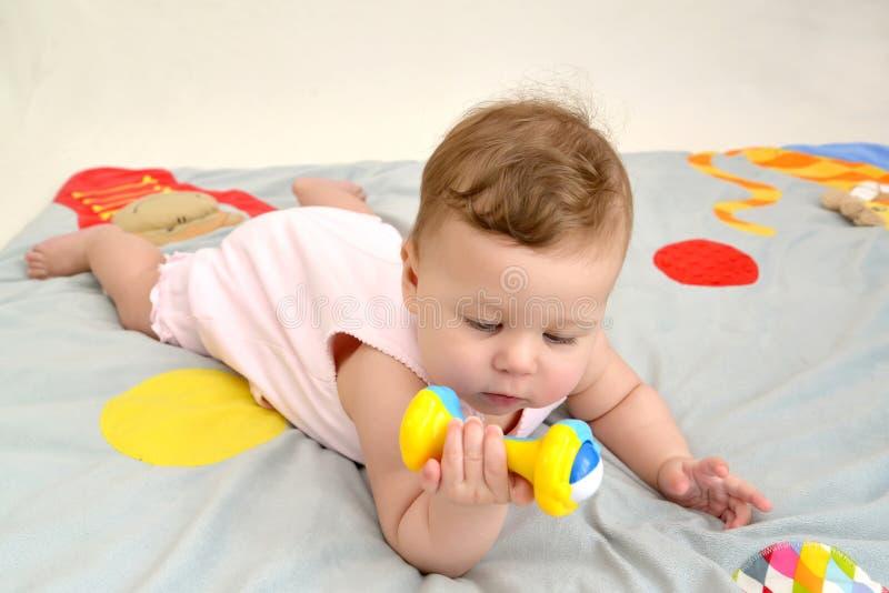 A criança pequena olha um chocalho, encontrando-se em um estômago fotos de stock royalty free