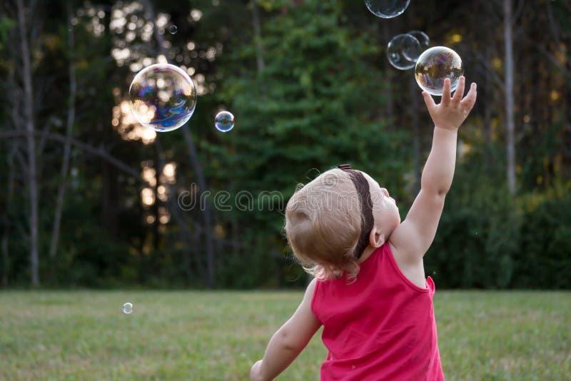 Criança pequena que alcança altamente para a bolha de sabão imagens de stock royalty free
