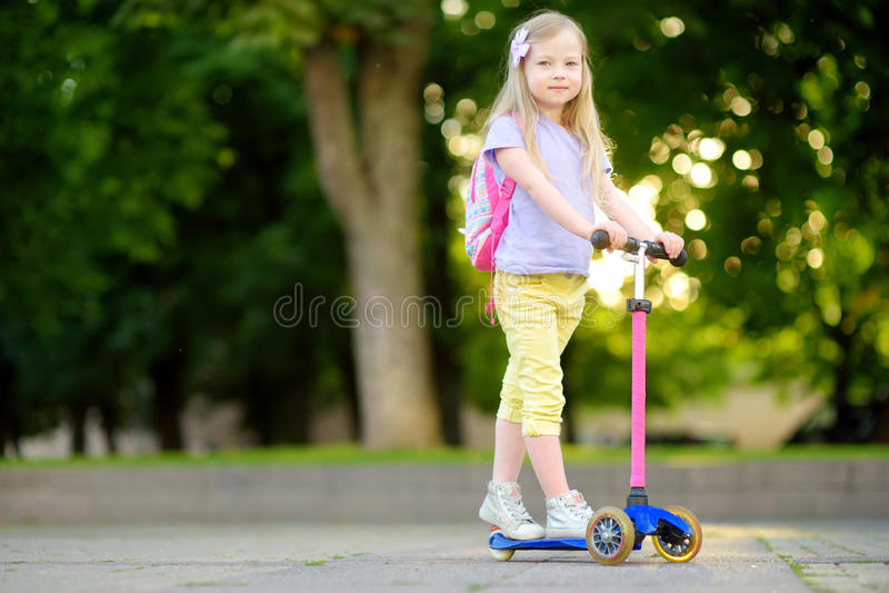 Criança pequena que aprende montar um 'trotinette' em um parque da cidade no dia de verão ensolarado Menina bonito da criança em  imagens de stock royalty free