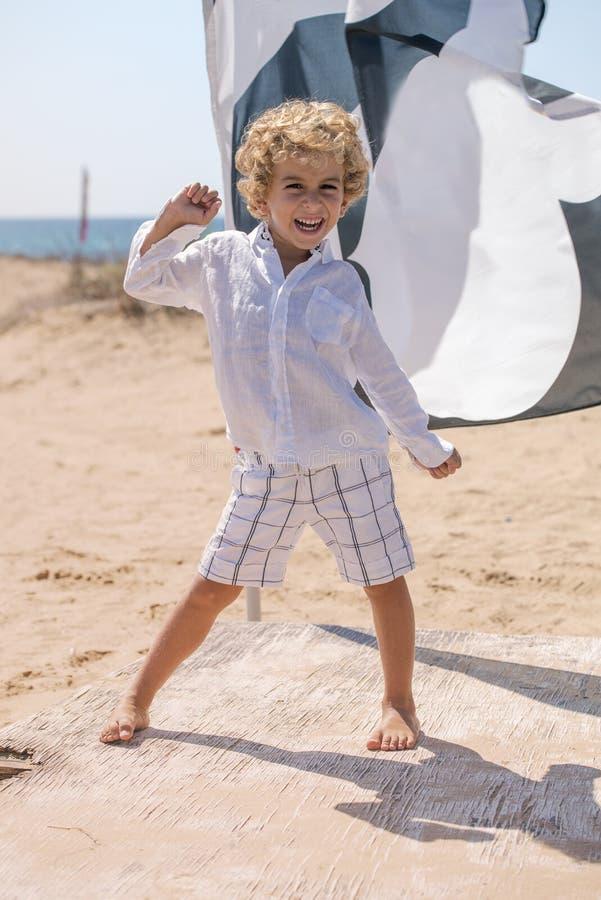 Criança pequena que caçoa estar em uma praia imagem de stock