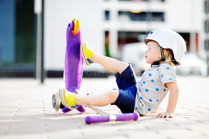Criança pequena que deixa de funcionar durante a aprendizagem montar o 'trotinette' fotos de stock royalty free