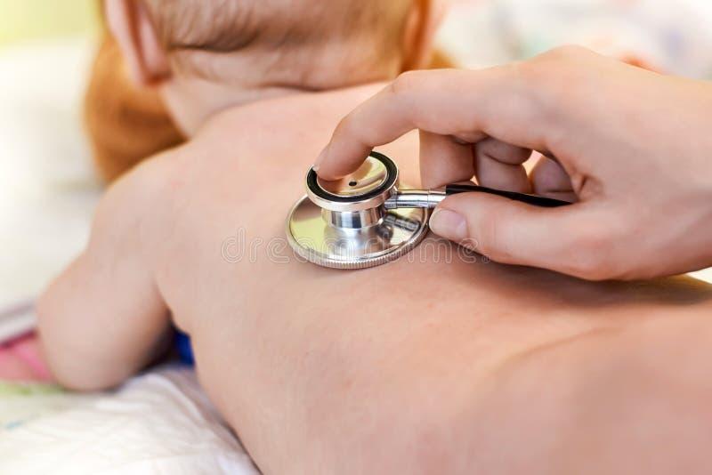 Criança pequena que está sendo examinada por um doutor foto de stock