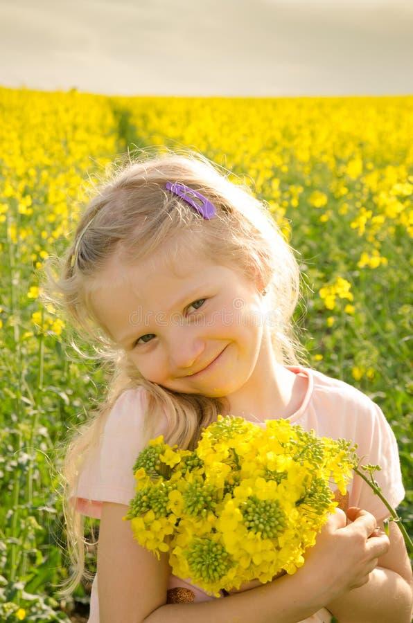 Criança pequena que guarda flores amarelas da colza fotografia de stock