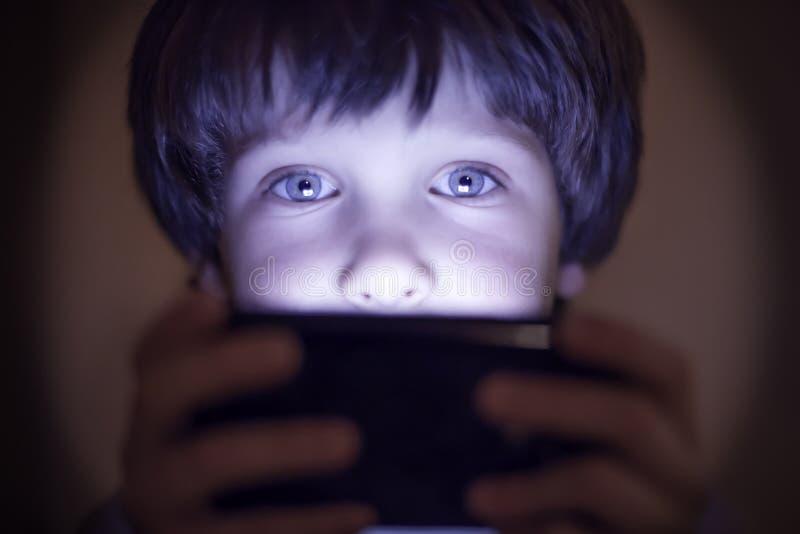 Criança pequena que joga em um smartphone imagem de stock