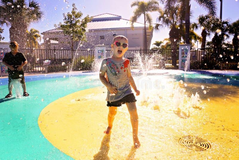 Criança pequena que joga na água no parque do respingo no dia de verão fotografia de stock royalty free