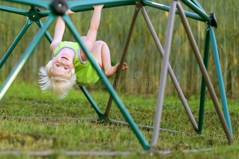 Criança pequena que joga no campo de jogos que escala em barras de macaco imagens de stock