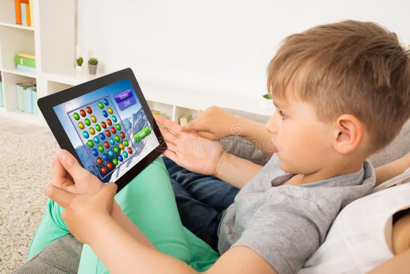 Criança pequena que joga o jogo na tabuleta de Digitas fotos de stock royalty free