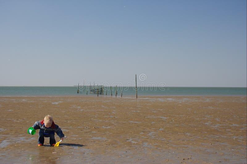 Criança pequena que joga a praia foto de stock royalty free