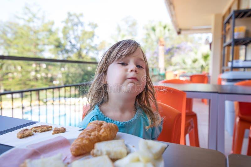 Criança pequena que olha desafiante no café da manhã fotos de stock