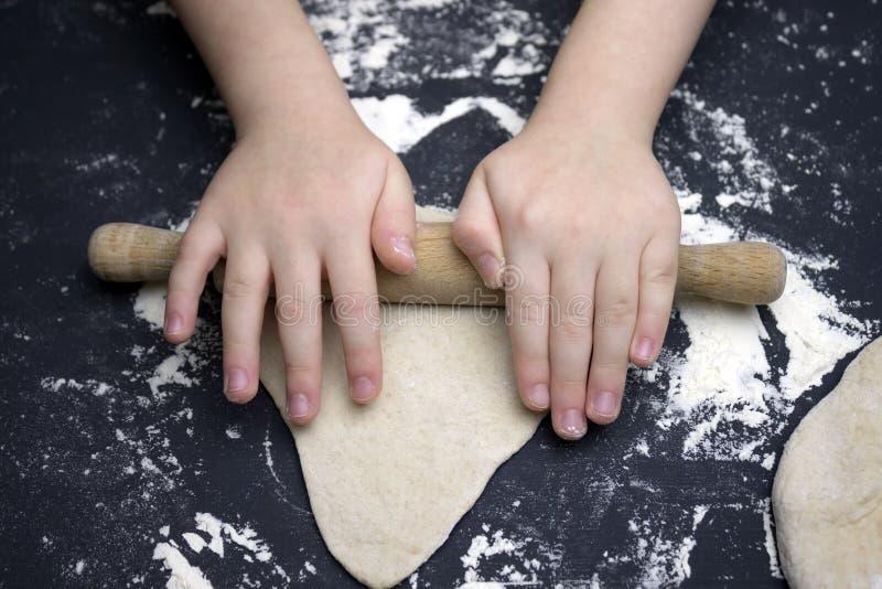 Criança pequena que prepara a massa para suportar Caçoe as mãos do ` s, a alguma farinha, a massa do trigo e o rolamento-pino na  foto de stock royalty free