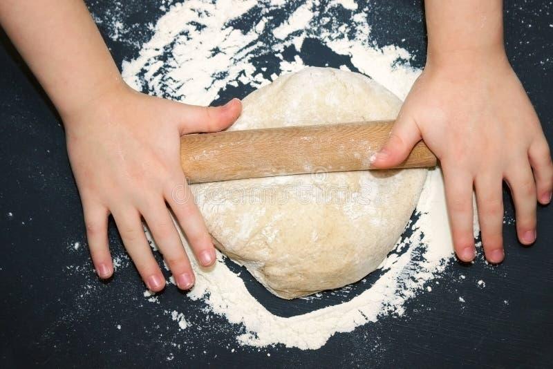 Criança pequena que prepara a massa para suportar Caçoe as mãos do ` s, a alguma farinha, a massa do trigo e o rolamento-pino na  fotos de stock royalty free