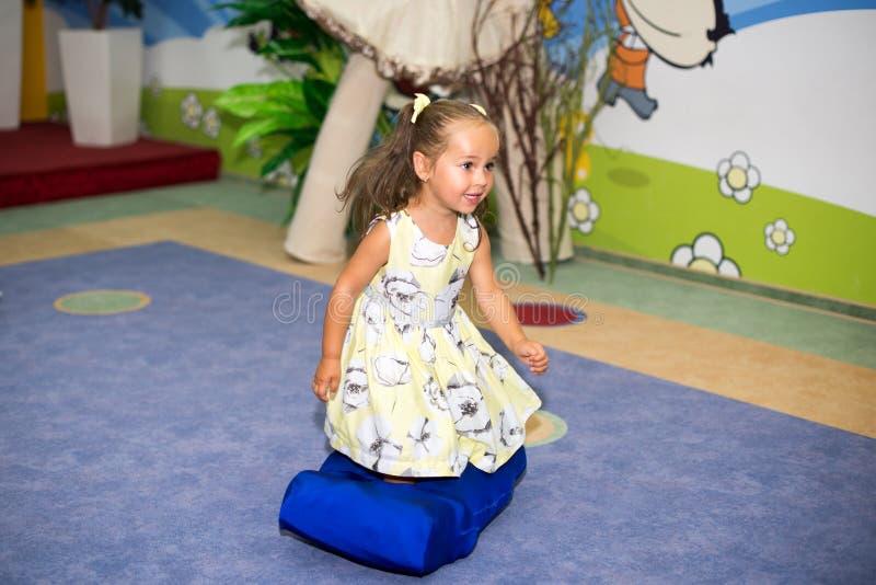 Criança pequena que salta no trampolim dentro no campo de jogos Menina ativa da criança que tem o divertimento no centro de espor fotos de stock royalty free