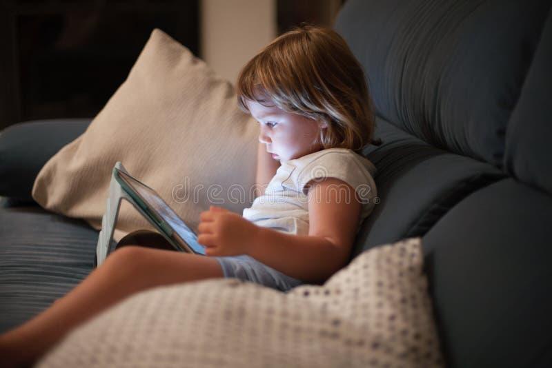 Criança pequena que senta-se confortavelmente na tabuleta de observação do sofá foto de stock royalty free