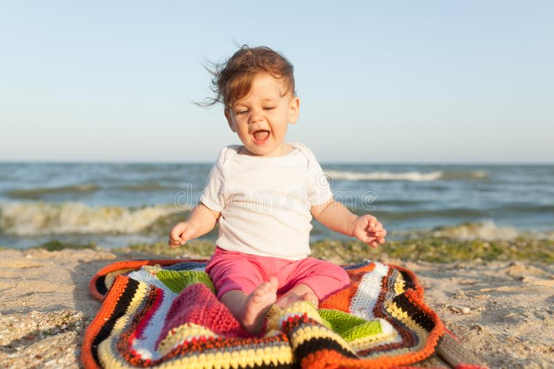 Criança pequena que senta-se em um tapete colorido no litoral alegre e feliz fotografia de stock royalty free