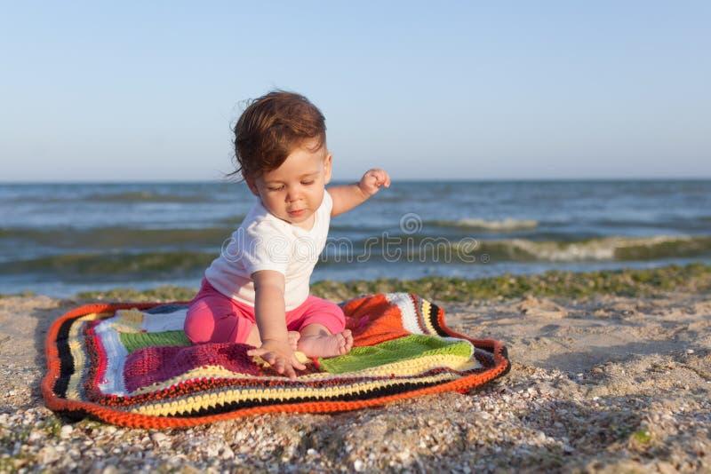 Criança pequena que senta-se em um tapete colorido no litoral alegre e feliz fotos de stock royalty free