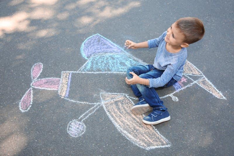 Criança pequena que senta-se perto do desenho de giz do avião ilustração do vetor