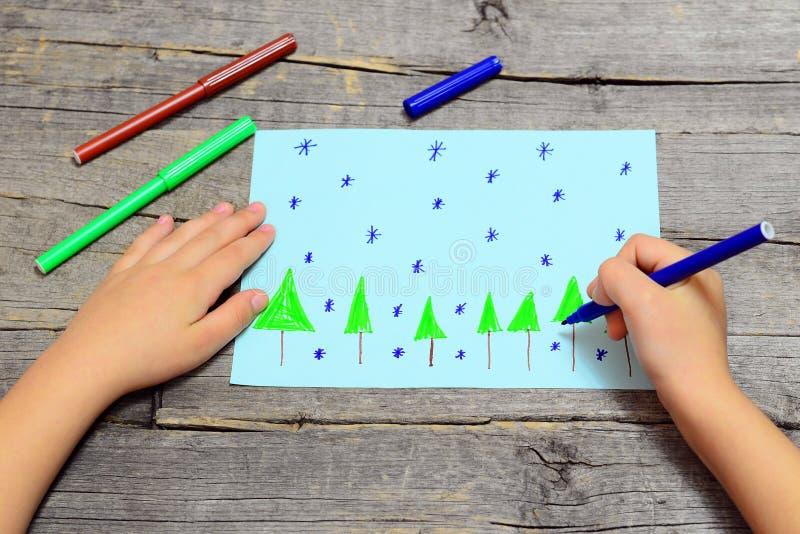 A criança pequena senta e tira árvores e flocos de neve de Natal no papel Criança que mantém o marcador azul disponivel e que tir fotos de stock royalty free
