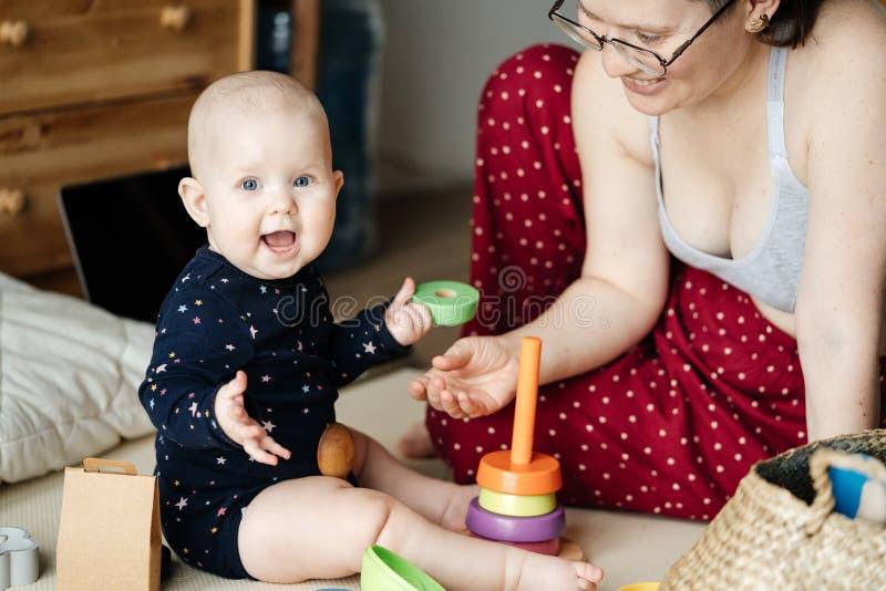 A criança pequena senta-se no assoalho e joga-se alegremente com os brinquedos coloridos com sua mãe no interior fotografia de stock royalty free