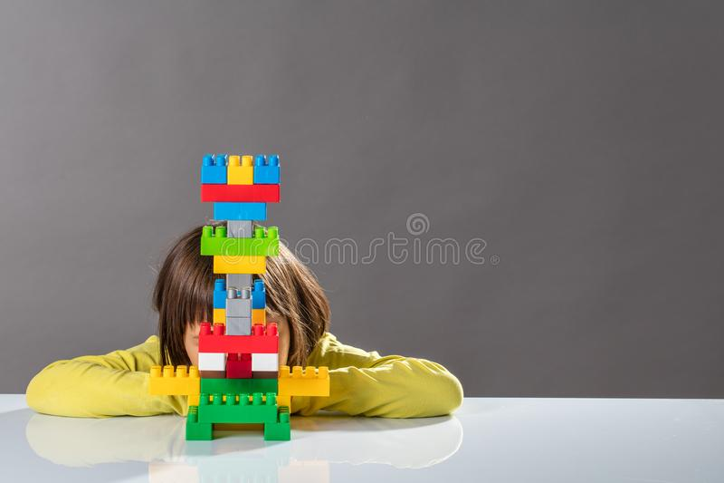 Criança pequena tímida que esconde atrás do brinquedo construído para a psicologia da criança fotos de stock